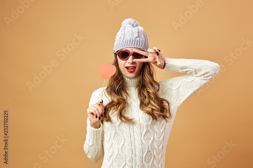da722690e36 Funny girl in sunglasses dressed in white knitted sweater and hat haves fun  with a red