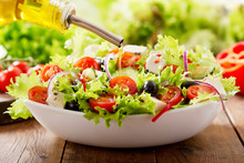 Cooking Salad. Olive Oil Pouring Into Bowl Of Fresh Salad