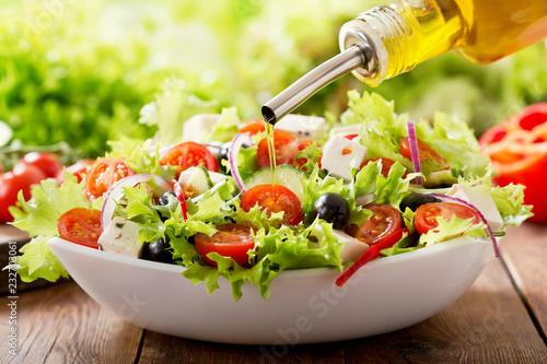 Obraz na plátně Cooking salad. olive oil pouring into bowl of fresh salad