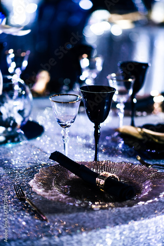 Tables set for an event party or wedding reception. luxury elegant table setting dinner in a restaurant. Black and gold glasses and dishes.