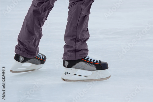 Photo  Close-up of ice skater's male feet on ice rink during ice hockey
