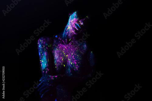 Bodypainting on nude girl painted with UV colors