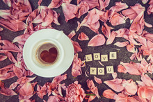 Flatlay Cup Of Coffee With Heart Shape Pattern And Message I Love You Spelled In Wooden Blocks With Pink Peony Flower Petals On Dark Background. Valentines Day, Good Morning Concept. Vintage. Top View