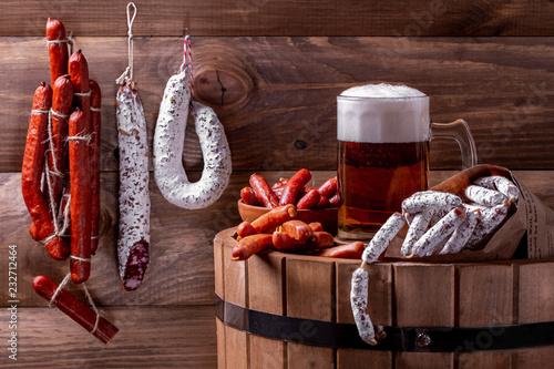 Tuinposter Bier / Cider кружка пива на дубовой бочке с колбасками разных сортов