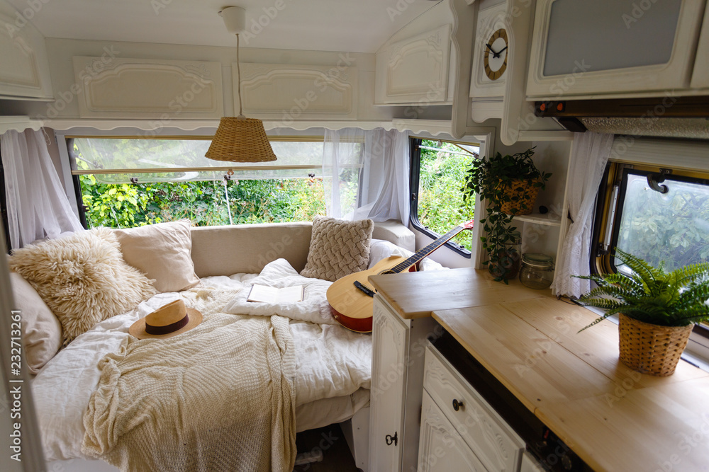 Fototapety, obrazy: Inside the camper van. Unfilled bed, pillows, guitar, book, hat, white wooden decoration of the house on wheels.