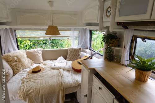 Spoed Fotobehang Kamperen Inside the camper van. Unfilled bed, pillows, guitar, book, hat, white wooden decoration of the house on wheels.