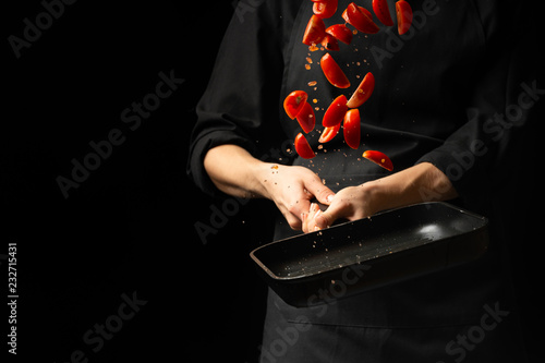 The chef prepares tomato sauce, fry the tomatoes, cherry tomatoes in a frying pan, freeze, for pasta, pizza. steps process on kitchen on black background copy text recipe.