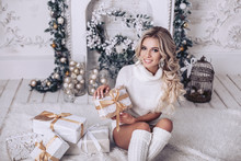 The Blonde Is Smiling Holding A New Year's Gift. White Fireplace In The Interior Decorated For Christmas With Fir Branches And Toys.