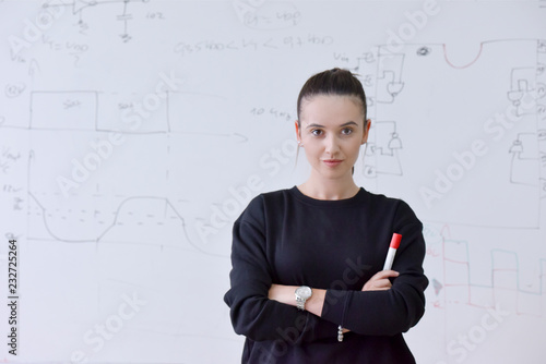 Young female student with pen in her hand  standing in front of a blank chalkboard and looking at the camera.