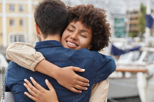 Photo  Pleased charming woman with Afro haircut, embraces passionately her close friend, have friendly relationship, meet outdoor, express love