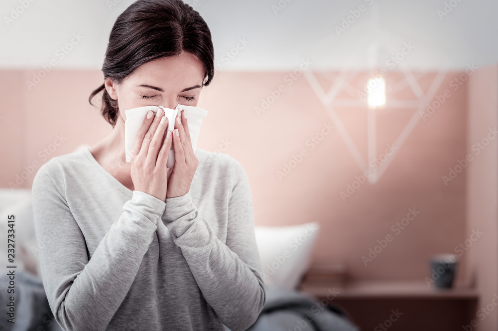 Fototapeta Feeling awful. Close up of young woman using a handkerchief while keeping her eyes closed and blowing her nose