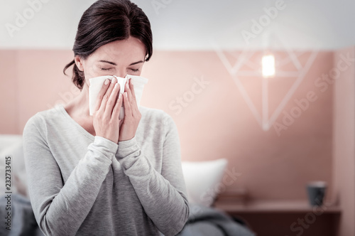 Fototapety, obrazy: Feeling awful. Close up of young woman using a handkerchief while keeping her eyes closed and blowing her nose