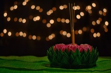 Banana Leaf Krathong That Have 3 Incense Sticks And Candle Decorates With Pink Lotus Flower For Thailand Full Moon Or Loy Krathong Festival Puts On Banana Leaves Isolated On Bokeh Lights Background.