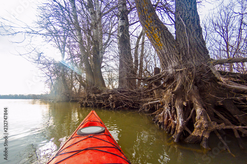 Foto  View from the red kayak on the river banks with autumnal trees in fall (winter) season