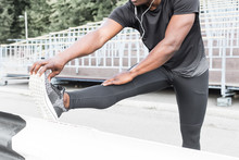 Concentrated African American Sportsman Warming Up And Stretching Legs On Pier