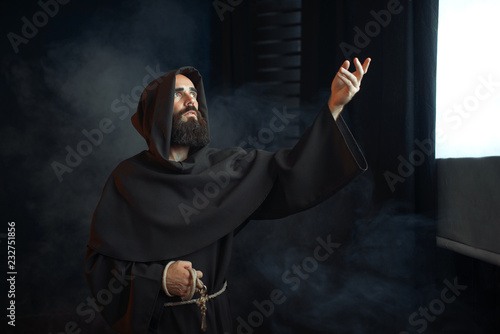 Fotomural Medieval monk praying against a window with light