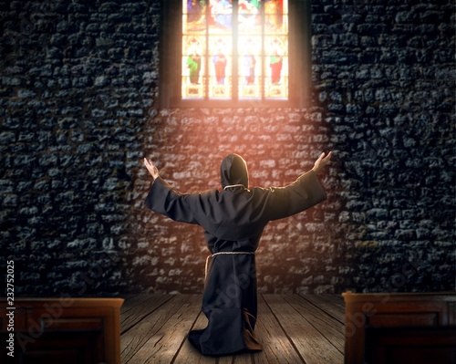 Medieval monk kneeling and praying in church Canvas-taulu