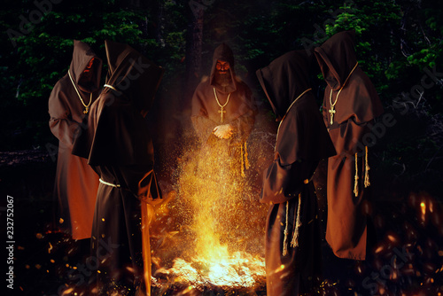 Medieval monks praying against a fire in the night Fototapeta
