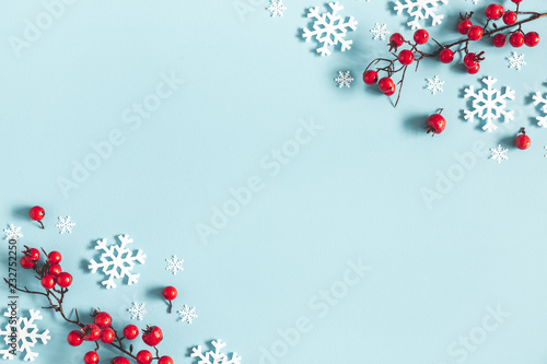 Christmas or winter composition. Frame made of snowflakes and red berries on pastel blue background. Christmas, winter, new year concept. Flat lay, top view, copy space