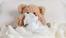 Cold, Flu Or Allergy. Cute Teddy In Bed, Covered With A Warm Blanket, Holding A Tissue