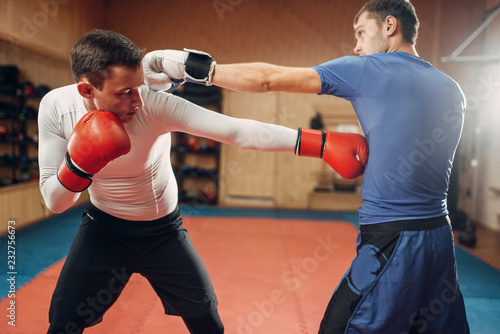 Photo  Two male kickboxers practicing on workout in gym