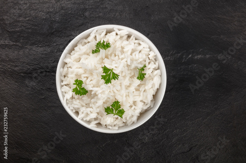 A photo of a bowl of cooked white long rice, shot from the top on a black background with copy space