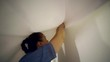 a middle-aged woman measures the canvas for the installation of a stretch ceiling
