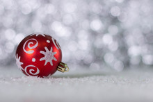 Red Ball Christmas Toy Close - Up On The Background Of Holiday Lights. Christmas Background With Space For Text.