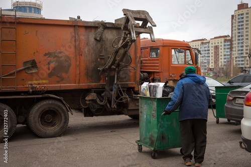 Fotografia, Obraz  The worker carries a container with garbage to the garbage collection machine during garbage collection on the streets of Krasnoyarsk