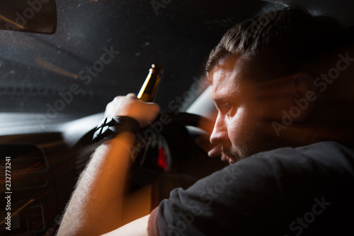 Drunk driver. Man drinking beer while driving a car Fototapet