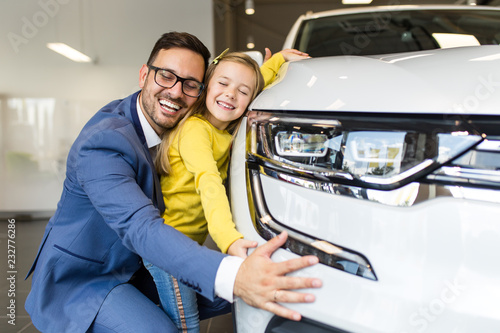 Father and daughter buying a new car at the car showroom.