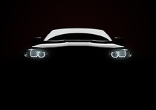 Front View Of A Generic And Brandless Modern Car With Lights On A Black Background