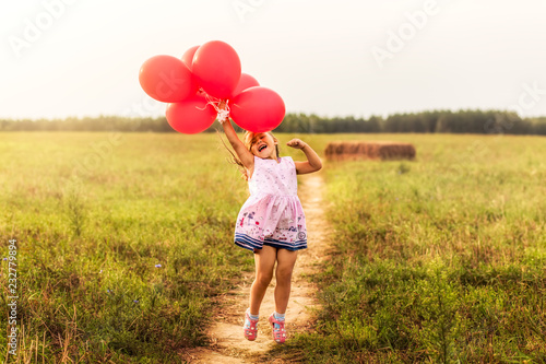 Photo  girl runs with red balloons in the summer in nature