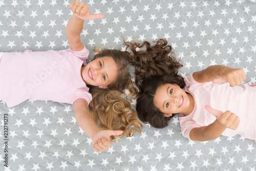 Amazing hair tips. Children curly hairstyle relaxing. Conditioner mask organic oil keep hair shiny and healthy. Keep hair curly even next morning. Girls children with long hair lay on bed top view