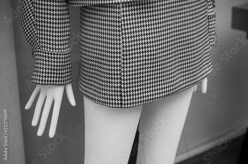 Photo  closeup of grey houndstooth skirt on mannequin in fashion store showroom for wom
