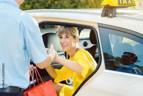 Fototapeta Taxifahrer hilft Frau beim Aussteigen aus dem Taxi obraz