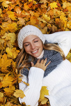 Attractive Woman With Closed Eyes Lying In Autumn Leaves