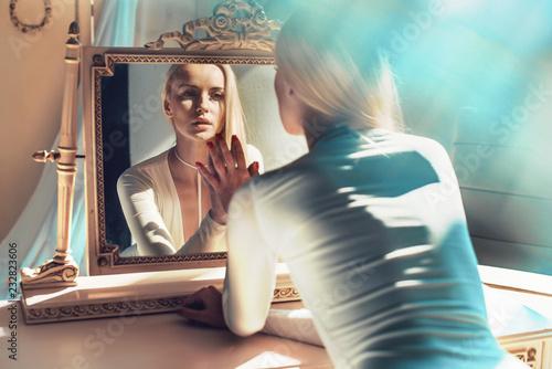 Obraz elegant blonde looking at her mirror reflection - fototapety do salonu