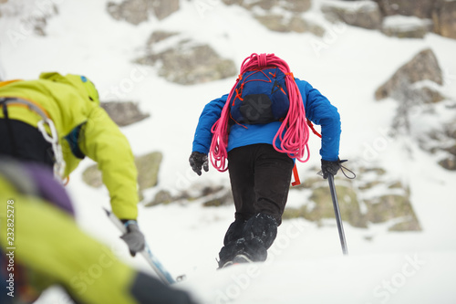 Poster de jardin Alpinisme Mountaineers climb the snow-covered mountain slope in bad weather.