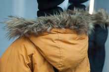 Closeup Of Yellow  Winter Coat With Fur Hood On Mannequin In Fashion Store Showroom