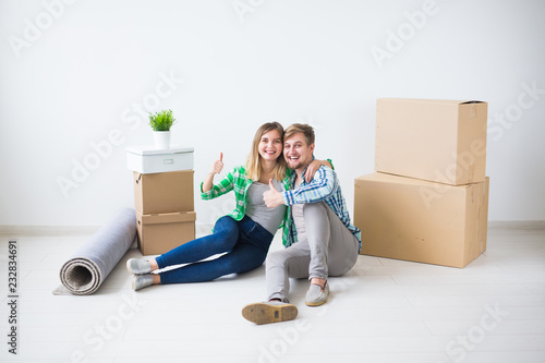 Fotografía  Relocation, new home and real estate concept - Young couple upacking in their ne