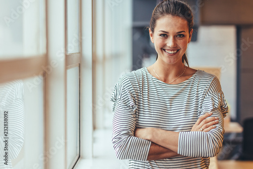 Photo  Smiling businesswoman standing with crossed arms