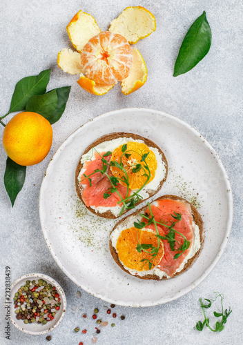 Delicious bread toasts with cream cheese (ricotta), salted smoked salmon, tangerine and pea sprouts. Gourmet snack