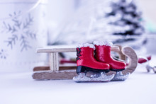 Christmas Background - Decorative Wooden Sleds And Small Red Skates On The Background Of Snow Cones And Christmas Trees