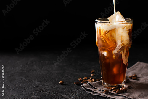 Canvastavla tall glass cold brew coffee with ice and milk on black or dark background