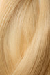 Texture of healthy blond hair as background, closeup