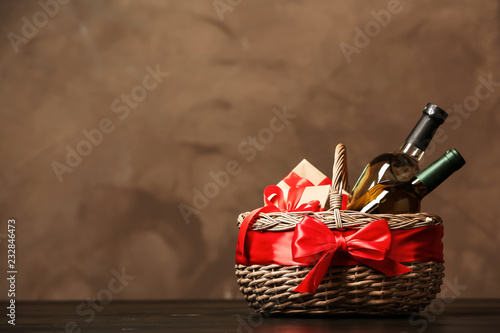 Gift basket with bottles of wine on dark background. Space for text