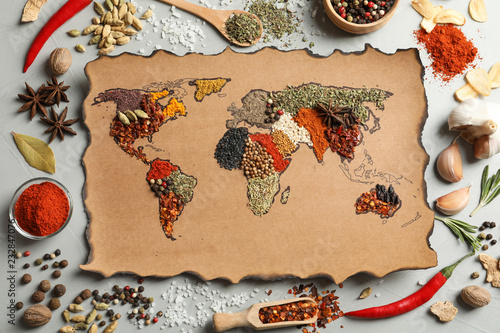 Paper with world map made of different aromatic spices on gray background, flat lay