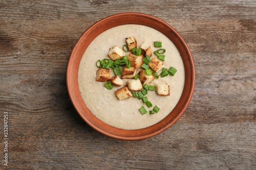 Bowl of fresh homemade mushroom soup on wooden background, top view