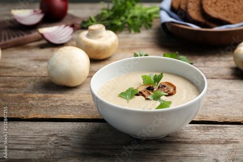 Bowl of fresh homemade mushroom soup on wooden table